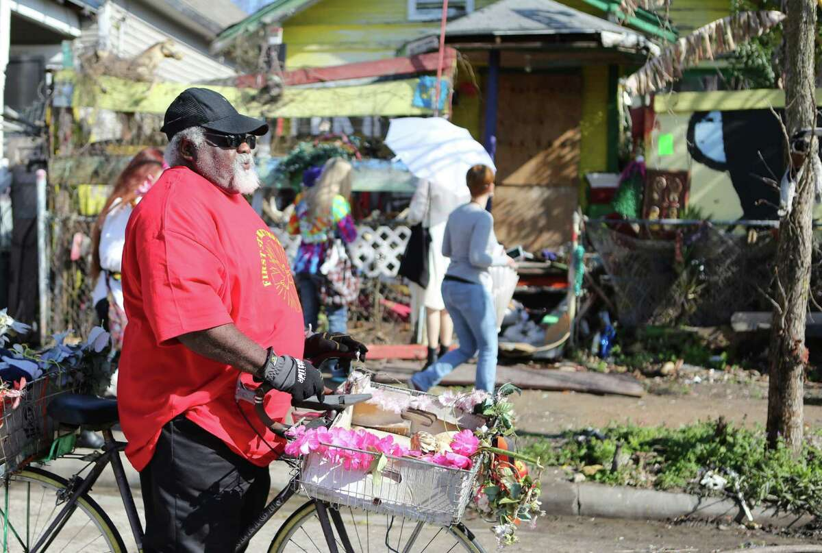 (Right) James Robbins holds on to the bicycle of Cleveland Turner, the Houston folk artist known as the Flower Man, upon arriving to his home which is set for demolition on Saturday, Feb. 7, 2015, in Houston.