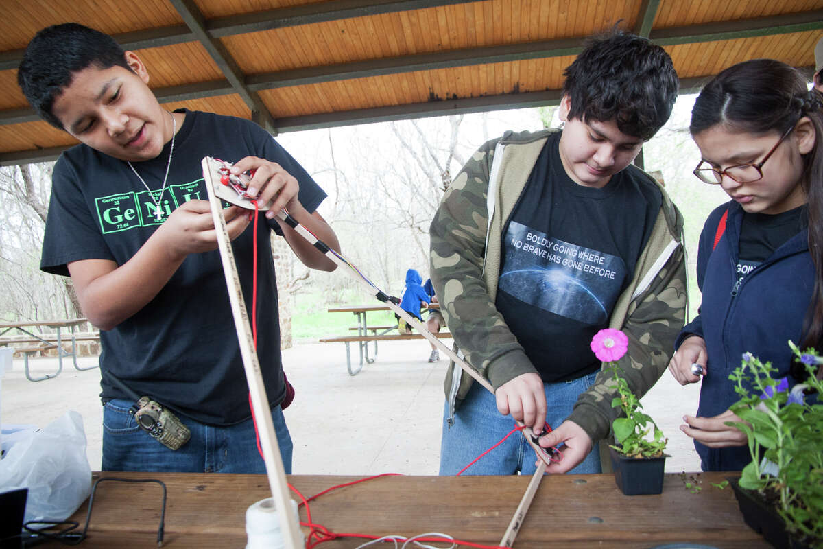 (From left) Julian Flores, 13, Jose Trevino, 12, and Alexis Manzano, 12, prepare a Delta Flight Frame for the launch of a weather balloon with the Harlandale Middle School Science Corps Saturday Feb. 7, 2015 at Medina River Natural Area.