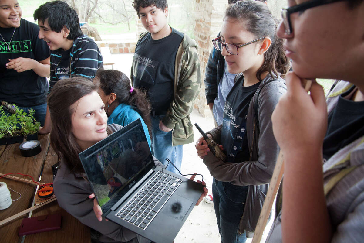 STEM Project Director Natasha Wilkerson shows students the angle of the camera that will be attached to the weather balloon Saturday Feb. 7, 2015 as part of the Harlandale Middle School Science Corps at Medina River Natural Area.