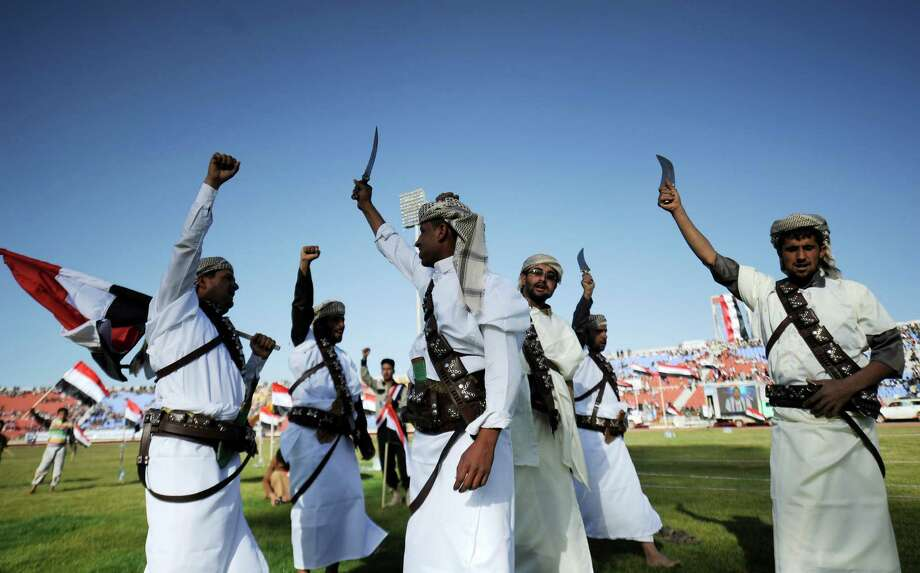 Supporters of Houthi Shiites, who took over the government of Yemen, wave traditional daggers and chant slogans at a rally on Saturday. Photo: Hani Mohammed, STR / AP