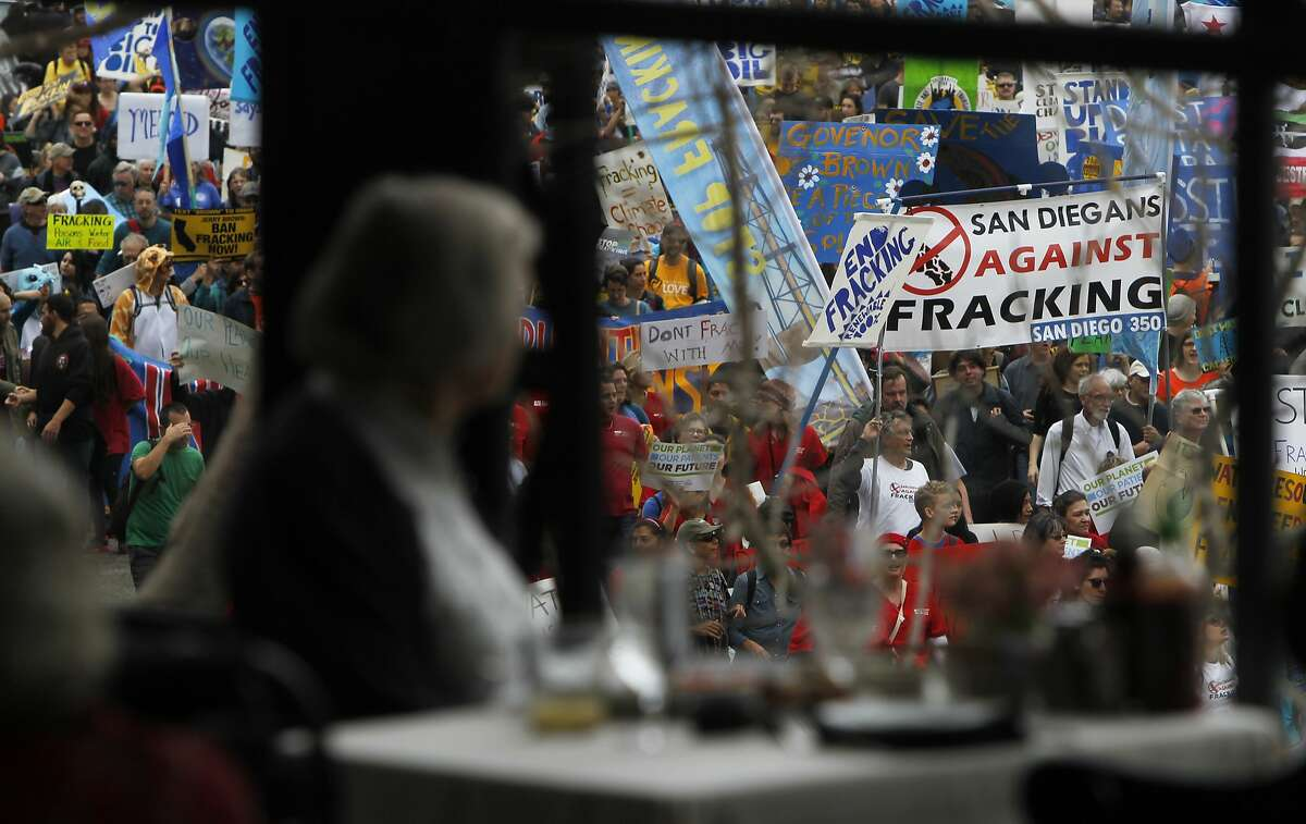 A woman watches through the restaurant window of Lake Merritt Hotel while thousands march down Lakeside Drive in Oakland, Calif. Saturday, February 7, 2015 during a protest against big oil company's fracking methods to extract gas, a process that has affects cities and towns all over the world.