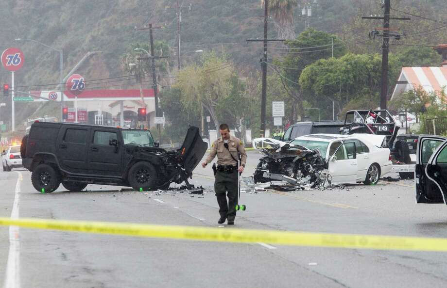 A Los Angeles County Sheriff's deputy investigates the scene of a collision involving several vehicles in Malibu, Calif. Officials said former Olympian Bruce Jenner was a passenger in one of the cars involved in the Pacific Coast Highway crash that killed one person. Jenner's publicist said the celebrity was not hurt.  Photo: Ringo H.W. Chiu, FRE / FR170512 AP