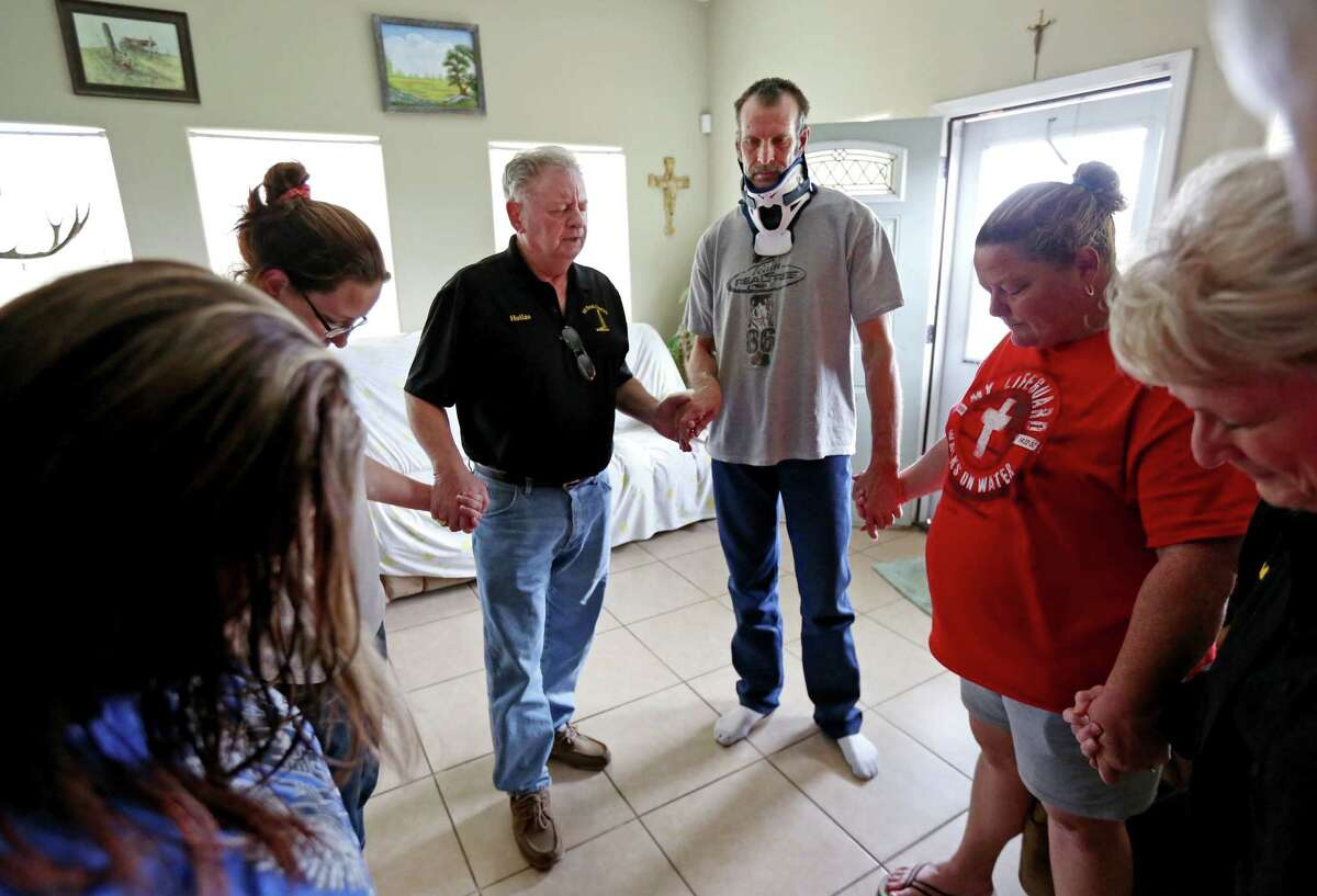 Hollas Hoffman, in black shirt, co-founder of Oil Patch Chaplains, prays with John Salmon, a truck driver with Wrangler Trucking, and his wife Rebecca Salmon, in red shirt, and others in Gonzales.