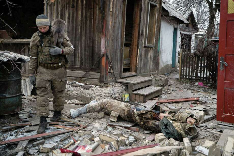A pro-Russian rebel carries a cat as he walks past a dead Ukrainian soldier on February 7, 2015 in the eastern Ukrainian town of Vuglegirsk in the Donetsk region. Kiev on on February 7 accused pro-Russian Ukrainian separatists of massing forces for fresh offensives, with seven civilians and five soldiers killed in the latest fighting in the east.   AFP PHOTO/ ANDREY BORODULINANDREY BORODULIN/AFP/Getty Images Photo: ANDREY BORODULIN / AFP