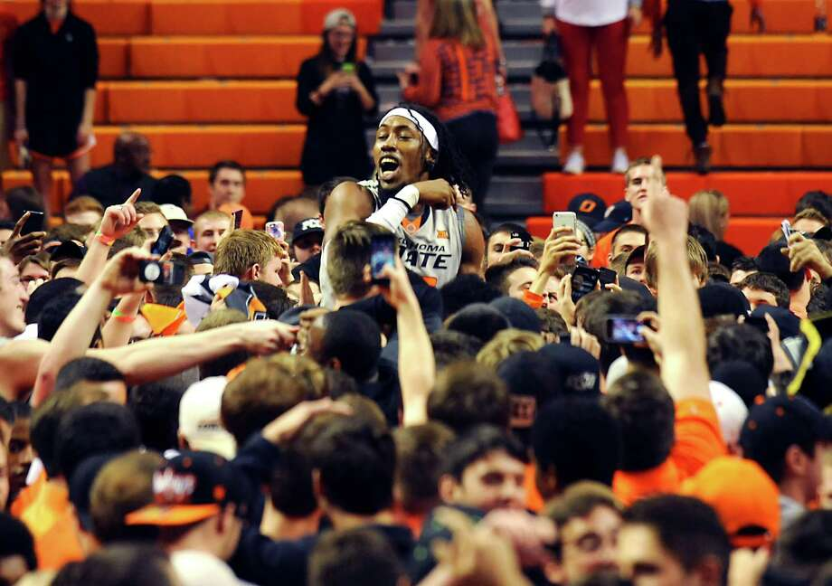 Oklahoma State's 7-foot center Anthony Allen Jr. rises to the occasion as he celebrates with fans Saturday after the Cowboys' 67-62 upset of No. 8 Kansas at Stillwater, Okla. Photo: Brody Schmidt, FRE / FR79308 AP