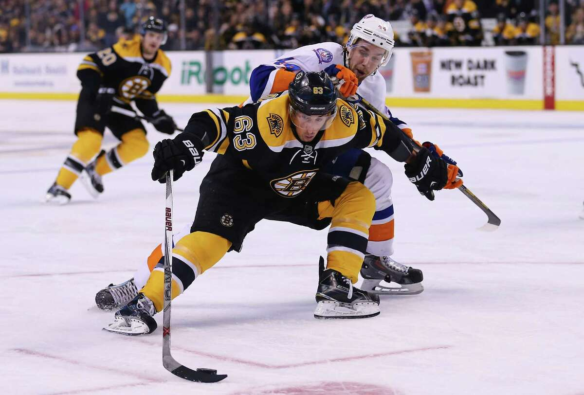 BOSTON, MA - FEBRUARY 07: Brad Marchand #63 of the Boston Bruins shields the puck from Calvin de Haan #44 of the New York Islanders during the third period at TD Garden on February 7, 2015 in Boston, Massachusetts. The Bruins defeat the Islanders 2-1. (Photo by Maddie Meyer/Getty Images) ORG XMIT: 507049345