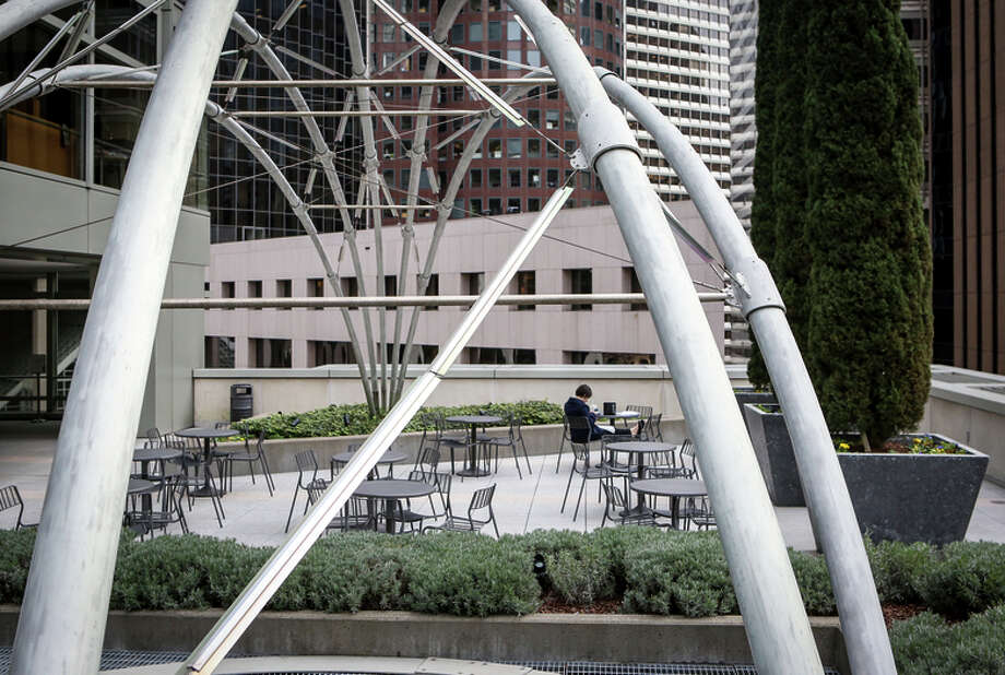 Allegra Thomas takes a break from her nearby office to sit in the quiet open space at 150 California St. Photo: Amy Osborne / The Chronicle / ONLINE_YES