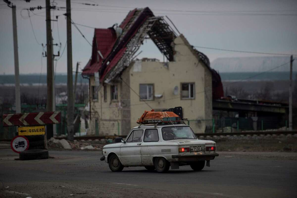 A car passes a damaged house near Slovyansk, eastern Ukraine, Saturday, Feb. 7, 2015. Ukraine's president pushed Saturday for a quick cease-fire in his country's troubled east, insisting that the conflict must be resolved and not