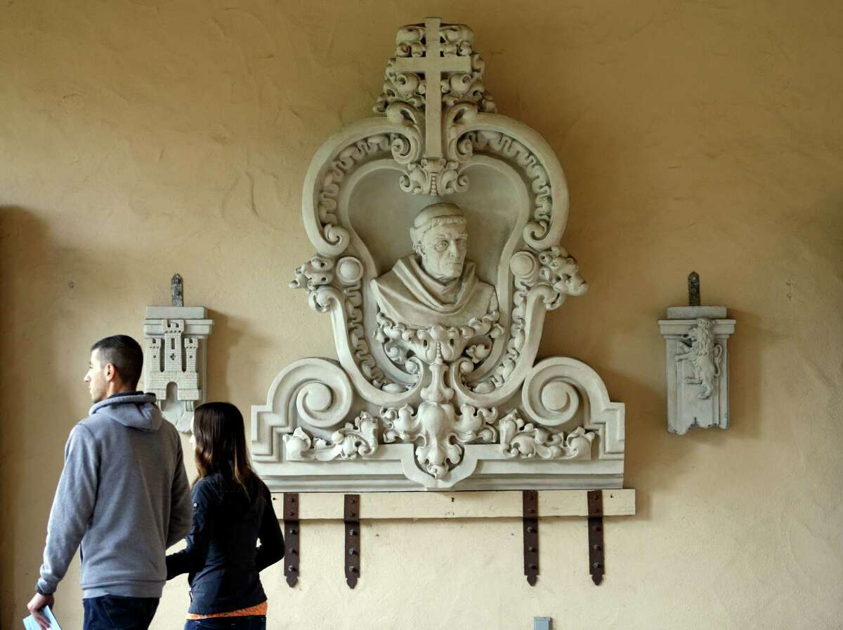 In this Jan. 30, 2015 image, a couple pass a bust of the late Franciscan missionary Junipero Serra at Balboa Park in San Diego. Pope Francis' announcement that he will canonize Serra is meeting resistance by some in California and beyond, as critics say he wiped out native populations, enslaved converts and spread disease. (AP Photo/Gregory Bull)