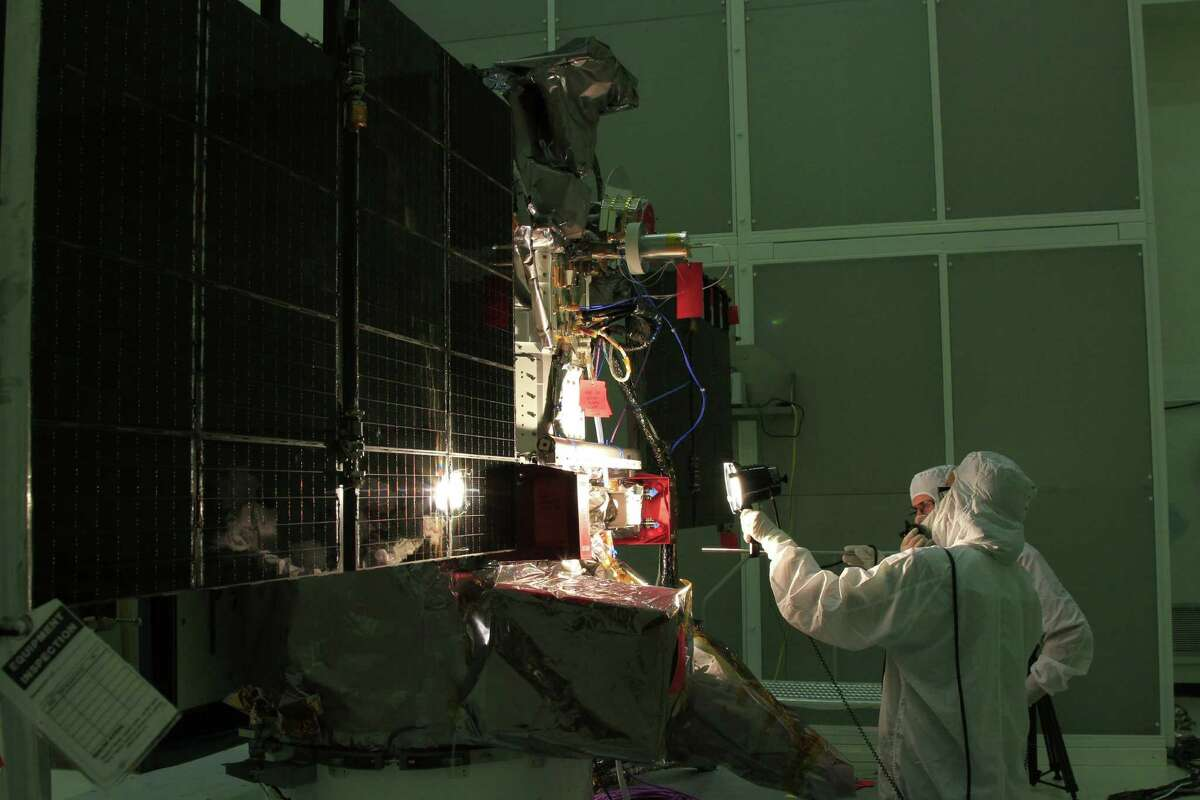 Workers conduct a light test on the solar arrays of the Deep Space Climate Observatory satellite at a NASA facility in Cape Canaveral, Fla.