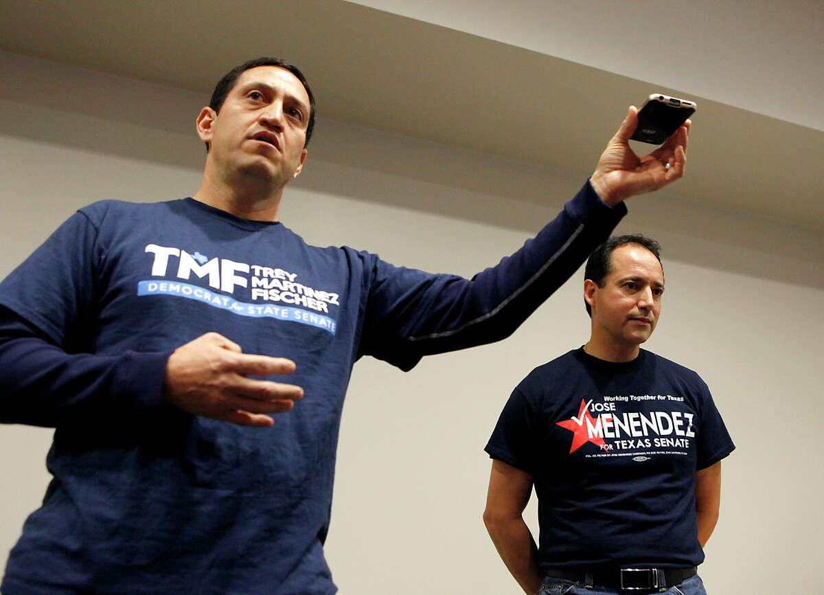 State Senate District 26 candidate Trey Martinez Fischer (left) plays a message from Henry Cisneros after a question was brought up to him about a claim that Cisneros was endorsing him as Jose Menendez listens Saturday Feb. 7, 2015 during the Northeast Bexar County Democrats meeting at Tri Point. Early voting for the special election runoff begins on Monday, Feb. 9.