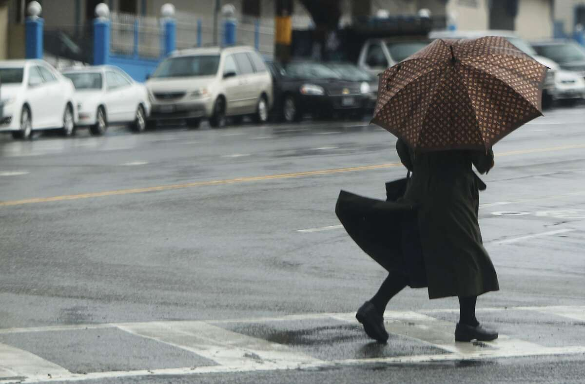 A woman scurries across Sagamore Street with and umbrella in San Francisco, Calif Sunday, February 8, 2015 after a rain storm soaked the Bay Area overnight Saturday and early Sunday morning