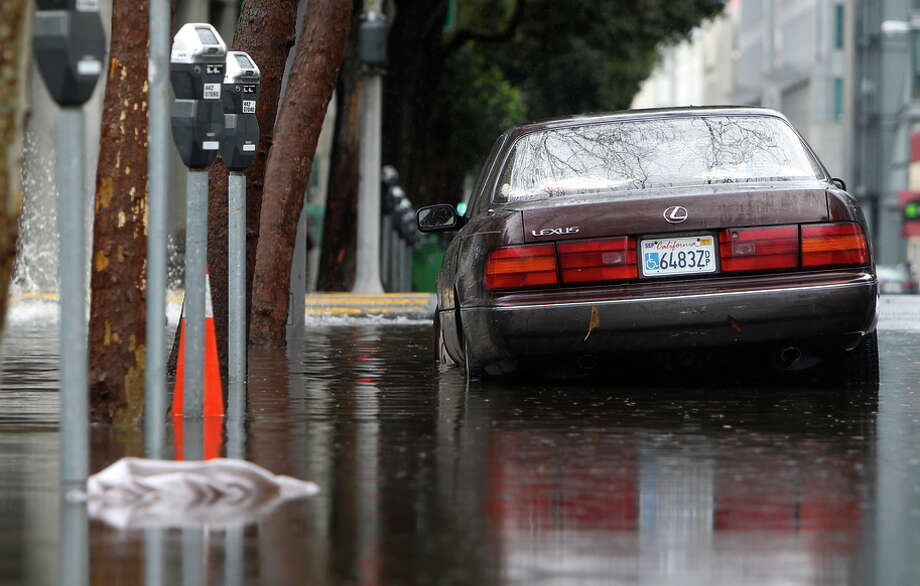 A parked car is partially submerged in floodwaters at the corner of Franklin Street and Golden Gate Avenue in S.F. Photo: Jessica Christian / The Chronicle / ONLINE_YES