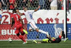 Clint Dempsey (8) slips the ball past sprawling Panama goalie Jaime Penedo to score the Americans' second goal.