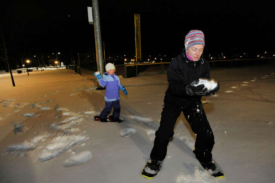Renata Bomash, 7, throws a snowball at her mother, Lyudmila German, who is preparing for retaliation while they snowshoe through Scalzi Park before a snow storm hits Stamford, Conn., on Sunday, Feb. 8, 2015. Photo: Jason Rearick / Stamford Advocate