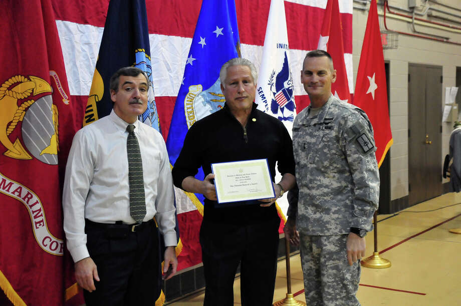 Division of Military and Naval Affairs Lance Ignmire displays the Adjutant General Award he received from Mike Friess, left, Division of Military and Naval Affairs special assistant, and Maj. Gen. Pattrick Murphy, adjutant general of state military forces.
