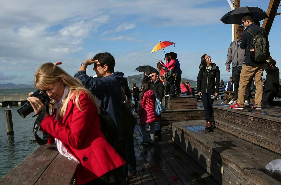 Tourists are not deterred by the rain and even get a bit of sunshine in the afternoon at Pier 39 in San Francisco, Calif., on Sunday, February 8, 2015. Photo: Amy Osborne, The Chronicle