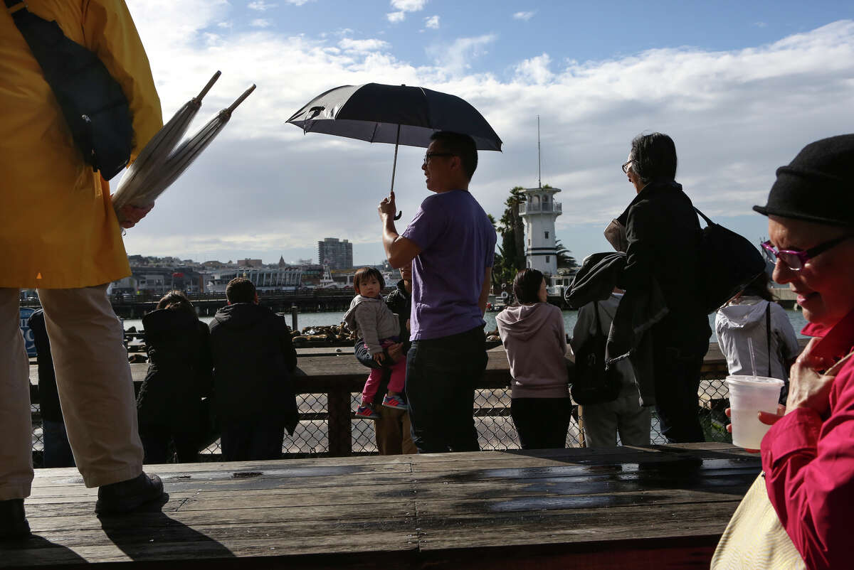 Tourists turned out at Pier 39 on Sunday despite the rain, and got a bit of sunshine during a break between storms.