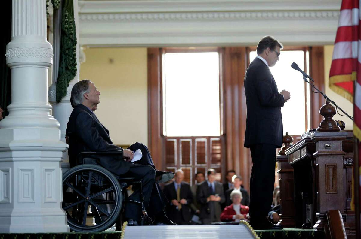 In this Jan. 5 file photo, Gov.-elect Greg Abbott, left, listens to Gov. Rick Perry during an oath of office ceremony for new Attorney General Ken Paxton.