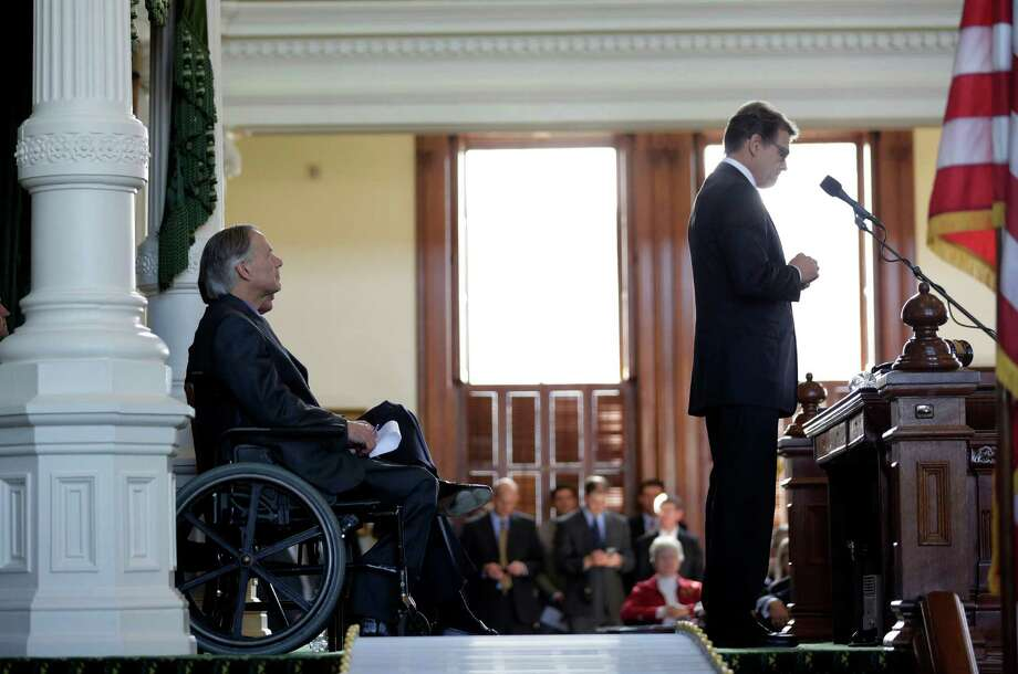 In this Jan. 5 file photo, Gov.-elect Greg Abbott, left, listens to Gov. Rick Perry during an oath of office ceremony for new Attorney General Ken Paxton. Photo: Eric Gay, STF / AP