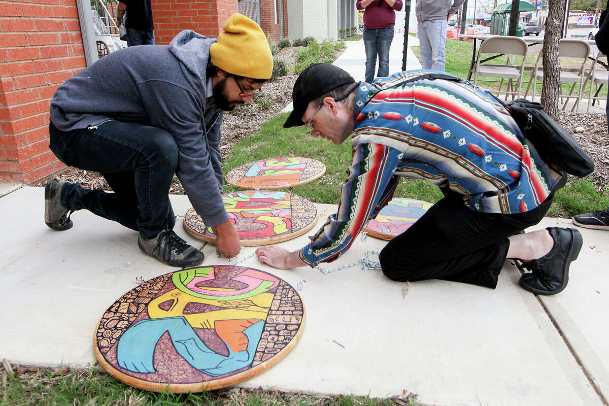 Victor Hernandez (left) and Blair Wilson installed a hand-painted sign in December for the grand opening of Nina Donley's art gallery, Zac Cimi Arte, at the Gardens at San Juan Square.