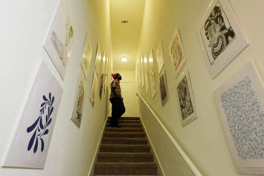Brian Pearson inspects pieces by Blair Wilson displayed in a stairwell during the grand opening for Zac Cimi Arte, an art gallery owned by Nina Donley at the Gardens at San Juan Square, 2003 S. Zarzamora #3104, on Saturday, Dec. 20, 2014. Donley currently is showcasing work from 16 local artists as well as her own at her gallery.  MARVIN PFEIFFER/ mpfeiffer@express-news.net Photo: Marvin Pfeiffer, Staff / San Antonio Express-News / Express-News 2014
