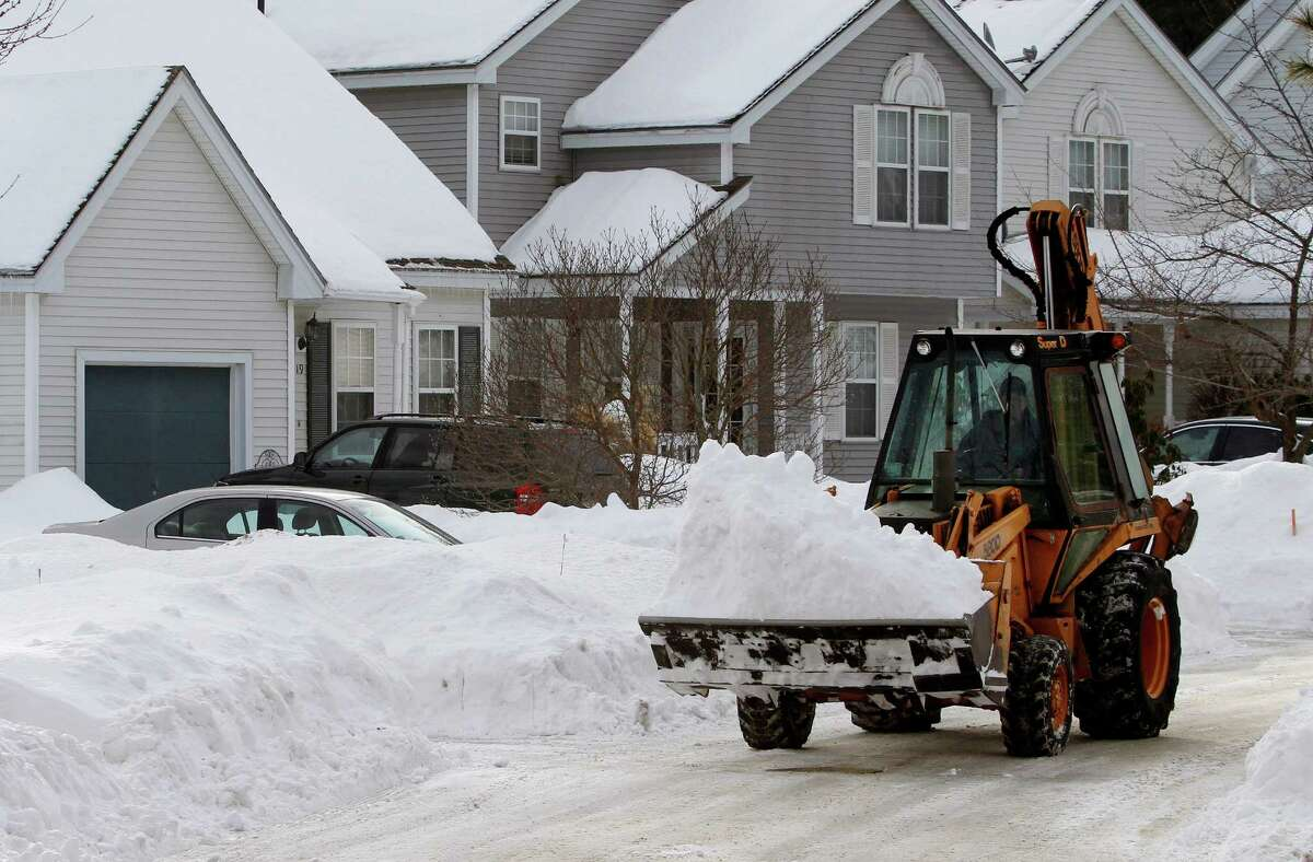 A worker uses a front-end loader to remove piled snow Saturday, Feb. 7, 2015, from a street in Marlborough, Mass. A long duration winter storm was forecast to begin Saturday night and remain in effect for a large swath of southern New England until the early morning hours Tuesday. (AP Photo/Bill Sikes) ORG XMIT: MAWS101