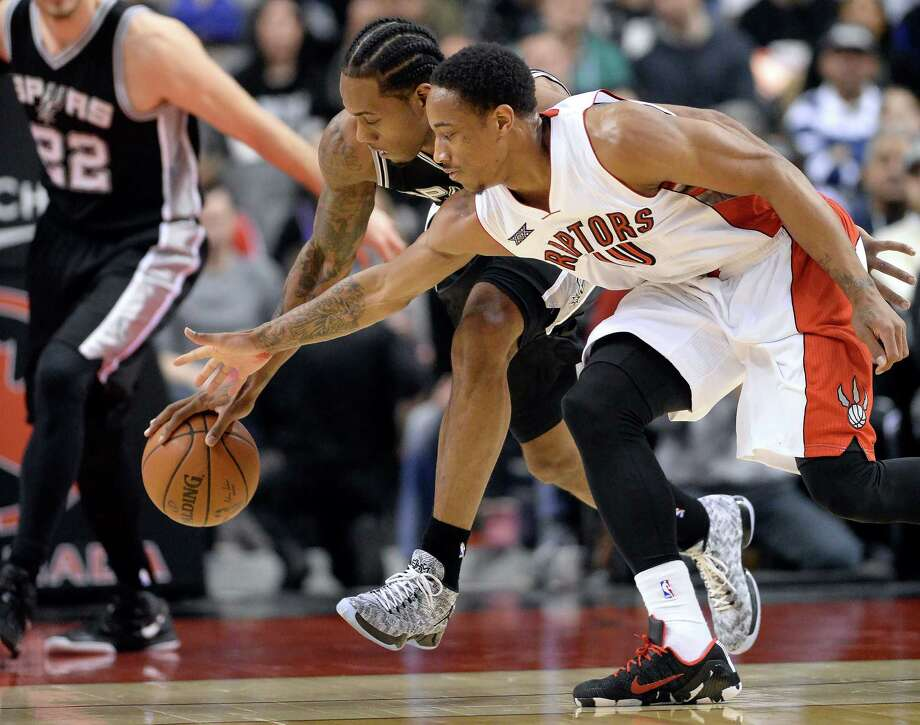 FILE -San Antonio Spurs' Kawhi Leonard chases the ball with Toronto Raptors' DeMar DeRozan. According to the sports betting site OddsShark.com, the Raptors are now the even-money favorite to land Leonard in a trade with the Spurs Photo: Frank Gunn /Associated Press / The Canadian Press