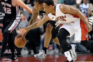 San Antonio Spurs' Kawhi Leonard chases the ball with Toronto Raptors' DeMar DeRozan during the first half.
