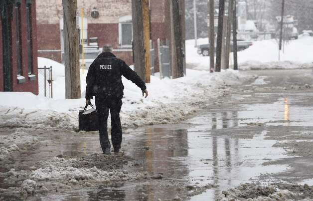 A Cohoes police officer arrives for work Monday amid a water-main break at the rear of City Hall. (Skip Dickstein / Times Union)