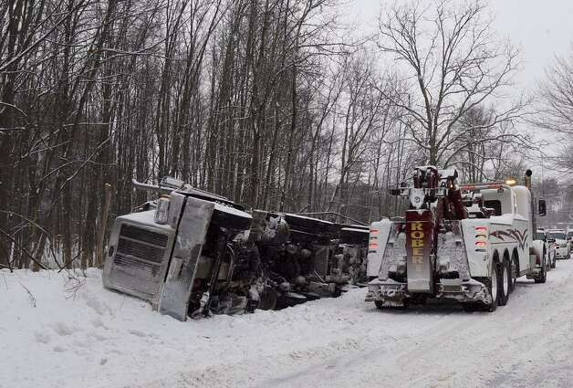 A tractor trailer rests on its side after it rolled on River Road in Bethlehem Monday. The truck lost its load of road salt. (Skip Dickstein / Times Union)