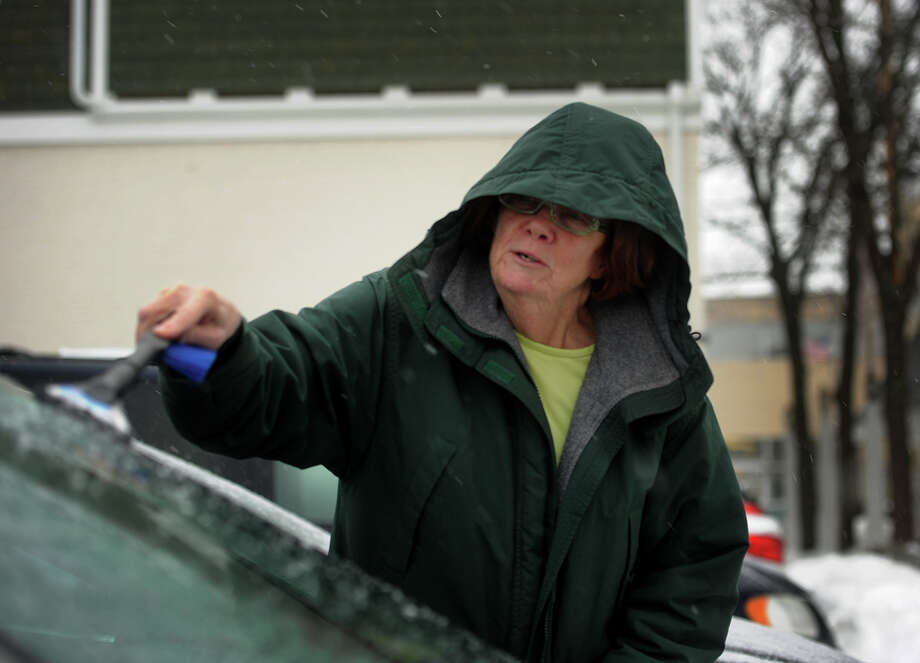 Kathy McGuire, of Milford, scrapes ice from her windshield as sleet and snow continues to fall in downtown Milford, Conn. on Monday, February 9, 2015. Photo: Brian A. Pounds / Connecticut Post