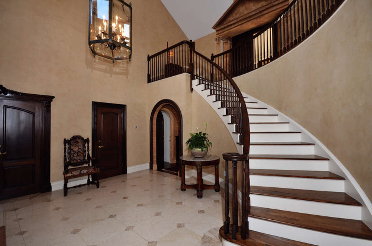 The two-story foyer has a marble floor and curved stairway.