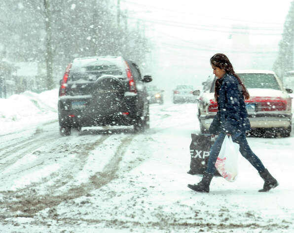 Bridgeport residents bear with the weather as another wintery mix hit the area on Monday, Feb. 9, 2015. Slick road conditions caused by sleet, freezing rain and some light snow forced many school district's to cancel classes again. Photo: Cathy Zuraw / Connecticut Post