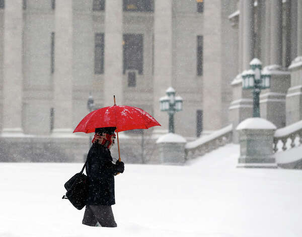 A pedestrian walks through morning snow past the State Education Building, background, and the Capitol, Monday, Feb. 9, 2015, in Albany, N.Y. Another round of snowy weather is starting off the week in much of upstate New York, with scores of schools closed and commuters facing a messy trip to work. (AP Photo/Mike Groll)  ORG XMIT: NYMG101 Photo: Mike Groll, AP / AP