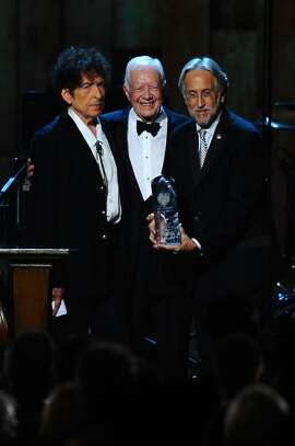 From left, President Jimmy Carter, Bob Dylan and Neal Portnow, President/CEO of The Recording Academy and President of The MusiCares Foundation, at the 2015 MusiCares Person of the Year show at the Los Angeles Convention Center on Friday, Feb. 6, 2015, in Los Angeles. (Photo by Vince Bucci/Invision/AP)