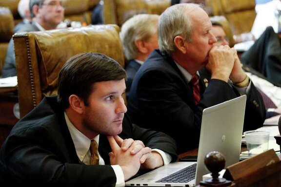 Republican Reps. John Lamar III, of Senatobia, left , and Ken Morgan of Morgantown, listen as House Education Committee Rep. Mark Baker, R-Brandon, presents House Bill 385, banning use of a Common Core-related test, wiping out high school exit exams in biology and U.S. history, and pushing the state Board of Education to adopt standardized tests published by the ACT organization in House Chambers, Thursday, Jan. 29, 2015 at the Capitol in Jackson, Miss. The House bill passed 116-3 and moves to the Senate for more debate. (AP Photo/Rogelio V. Solis)