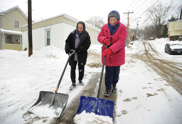 Neighbors Rita Chevarella, left, and Anna Scollin team up to clear snow from in front of their homes on 7th Street in Derby, Conn. on Monday, February 9, 2015. Photo: Brian A. Pounds / Connecticut Post