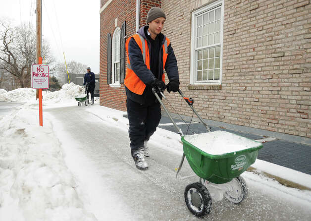 Public Works employee Vincent Faulkner, of Stratford, salts sidewalks outside Fire Department Headquarters on Main Street in Stratford, Conn. on Monday, February 9, 2015. Photo: Brian A. Pounds / Connecticut Post