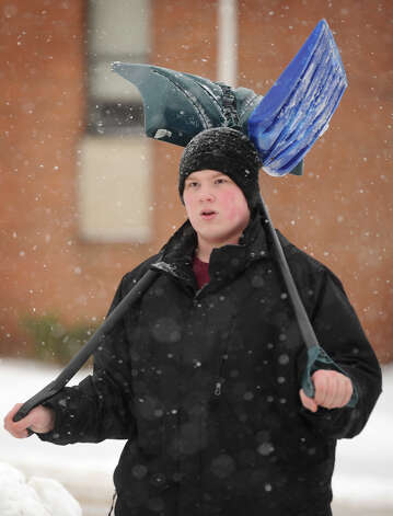 Ethan Denton, of Derby, walks with two snow shovels across 5th Street in Derby, Conn. on Monday, February 9, 2015. Photo: Brian A. Pounds / Connecticut Post