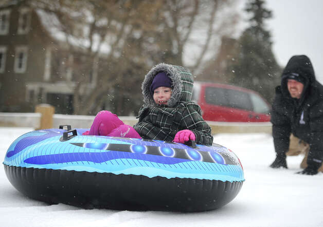Cailey Pecor, 8, of Stratford, gets a push down the hill from her dad Tom during an afternoon of tubing at Academy Hill in Stratford, Conn. on Monday, February 9, 2015. Photo: Brian A. Pounds / Connecticut Post