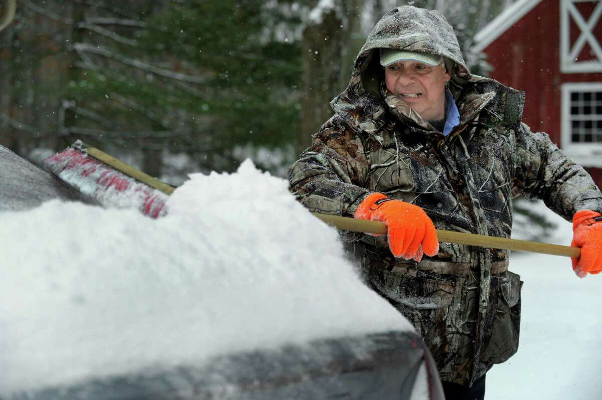 Bob Fusco brushes the snow off of a car in his driveway on Old Turnpike Road in Brookfield, Conn., Monday, February 9, 2015.