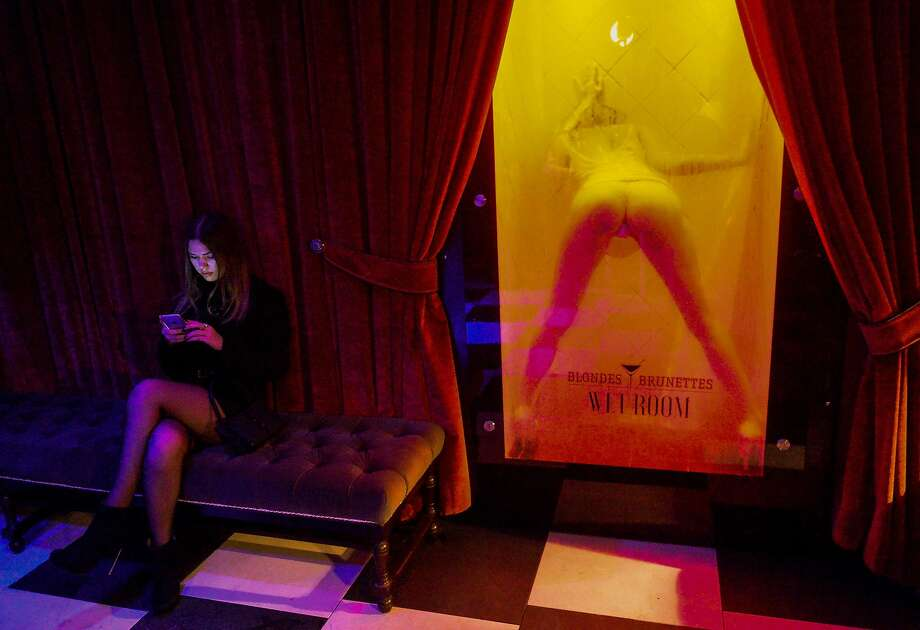 REDHEADS ARE NOT WELCOME:A guest to the Blondes and Brunettes nightclub in downtown Minsk is more interested in her cell phone than in the opening-night entertainment. Photo: Maxim Malinovsky, AFP / Getty Images