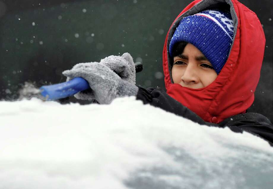 Johny Guallpa, 11, clears the ice and snow from a family car on Casper Street in Danbury, Conn., Monday, February 9, 2015. Photo: Carol Kaliff / The News-Times