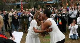 Yashinari Effinger kisses her spouse Adrian Thomas as they are declared a married couple by Rev. Ellin Jimmerson, minister to the community from Weatherly Baptist Church, Monday, Feb. 9, 2015 in Big Spring Park in Huntsville, Ala. Gay couples began getting married in Alabama on Monday morning, despite an 11th-hour attempt from the state's chief justice, an outspoken opponent of same-sex marriage, to block the weddings. (AP Photo/The Decatur Daily, Gary Cosby Jr.)