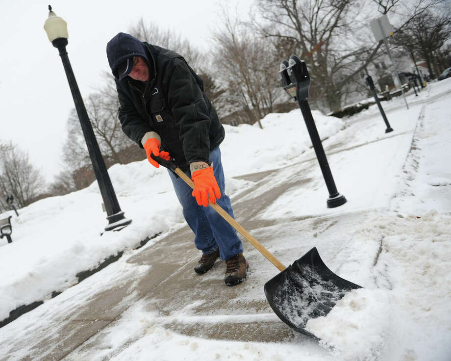 Jim McGuire, of Greenwich Parks & Recreation, shovels snow from the sidewalk along Greenwich Avenue in downtown Greenwich, Conn. Monday, Feb. 9, 2015.  The area received minimal snow accumulations, but quite a bit of freezing rain that created a layer of ice on the roads. Photo: Tyler Sizemore / Greenwich Time