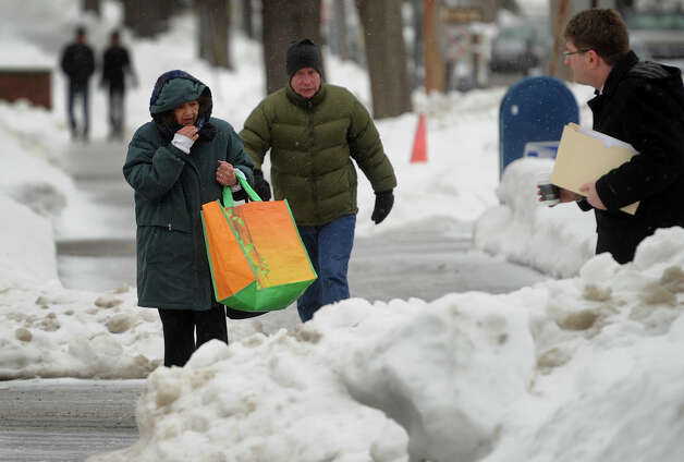 Pedestrians negotiate the snow and sleet covered sidewalks on River Street in downtown Milford, Conn. on Monday, February 9, 2015. Photo: Brian A. Pounds / Connecticut Post