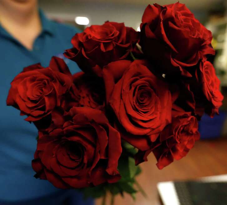 Wise couples agree up front about what each partner expects for Valentine's Day. Card and dinner? Card, flowers and dinner? This is best settled before the 14th. (Photo: Houston florists, including Elaine's Florist and Gift Baskets, have been busy  preparing Valentine flower arrangements.)