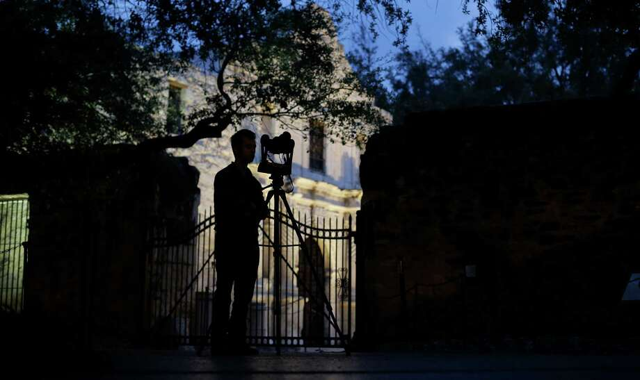 FILE - In this Jan. 9, 2014 file photo, Soheil Hamideh is silhouetted against the Alamo as he uses a camera to record images of the Alamo long barracks in San Antonio. A study by a team of Texas A&M-led architecture researchers employing lasers and digital images shows the iconic west facade of the Alamo in downtown San Antonio is slowly eroding. (AP Photo/Eric Gay, File) Photo: Eric Gay, STF / Associated Press / AP