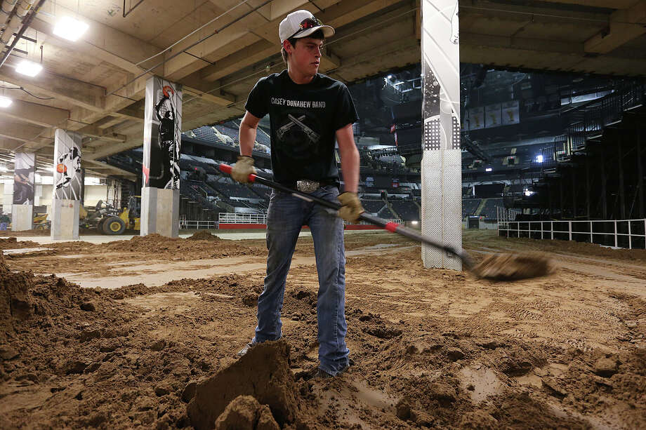 Charles Brumley, 17, of Lytle, packs dirt toward the edges Monday as workers turn the AT&T Center into the home of the San Antonio Stock Show & Rodeo. Photo: Jerry Lara /San Antonio Express-News / © 2015 San Antonio Express-News
